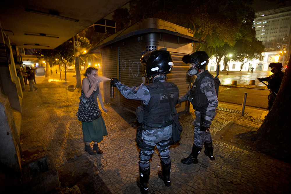 Military Police using pepper spray on a protester in Rio (AP Photo/Victor R. Caivano)